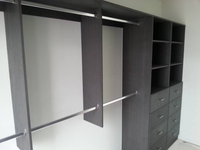 Walk-In-Wardrobe - Dark Brown Colour Board Shelving with Finger Pull Handles on the Banks of Colour Board Drawers & Chrome Hanging Rails
