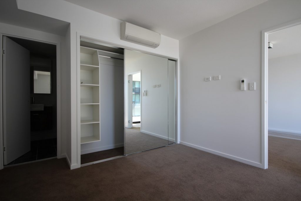 Frameless Mirror Robe Doors with Polished Silver Tracks & Built-in Wardrobe - Standard White Board Suspended Bank of Shelves, Top Shelf & Chrome Hanging Rod