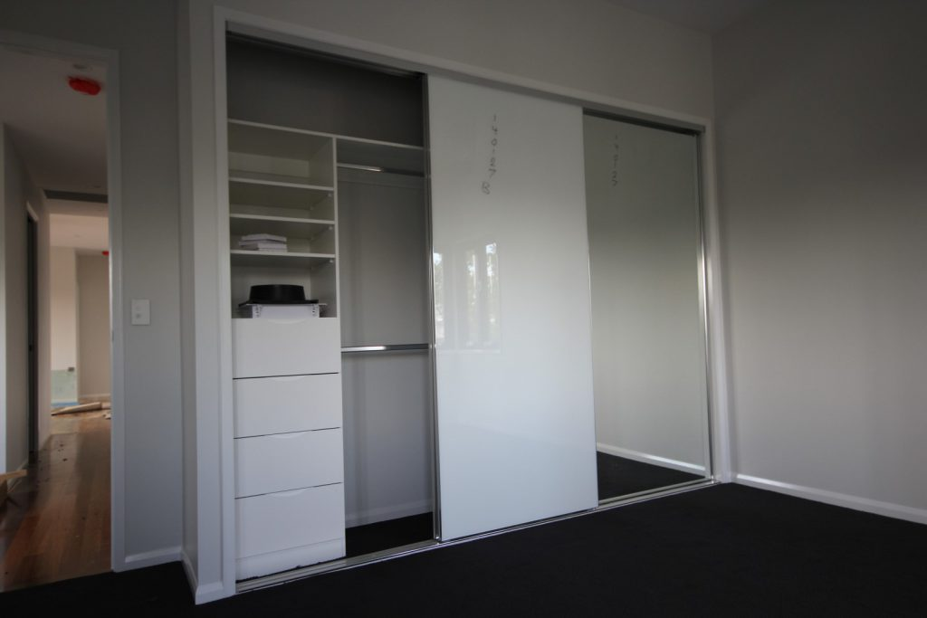 Frameless Super White & Mirror Robe Doors with Polished Silver Tracks & Built-in Wardrobe - Standard White Board Shelving with Finger Pull Handles on the Bank of Drawers and Chrome Hanging Rods