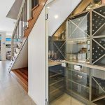 Wine Cellar - Frameless 10mm Glass Doors with Polished Silver Handles; Colour Board Shelving & a Mirror Splashback