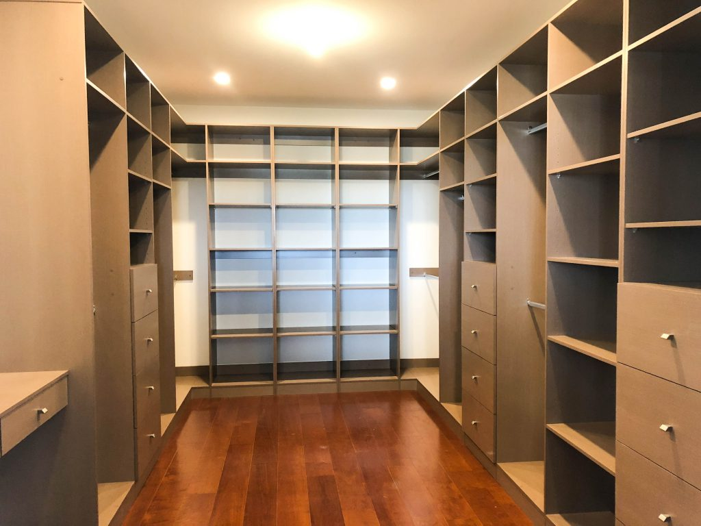 Walk-in-Wardrobe - Colour Board Shelving with Finger Pull Handles on the Banks of Drawers & Chrome Hanging Rods