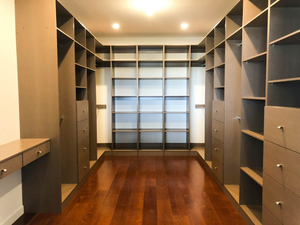Walk-in-Wardrobe - Hazel Strata Matt Colour Board Shelving with Finger Pull Handles on the Banks of Drawers & Chrome Hanging Rods