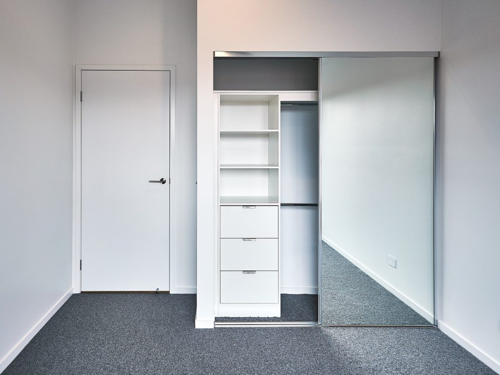 Frameless Mirror Robe Doors with Polished Silver Tracks & Built-in Wardrobe - Standard White Board Shelving with Finger Pull Handles on the Bank of Drawers & Round Chrome Hanging Rods