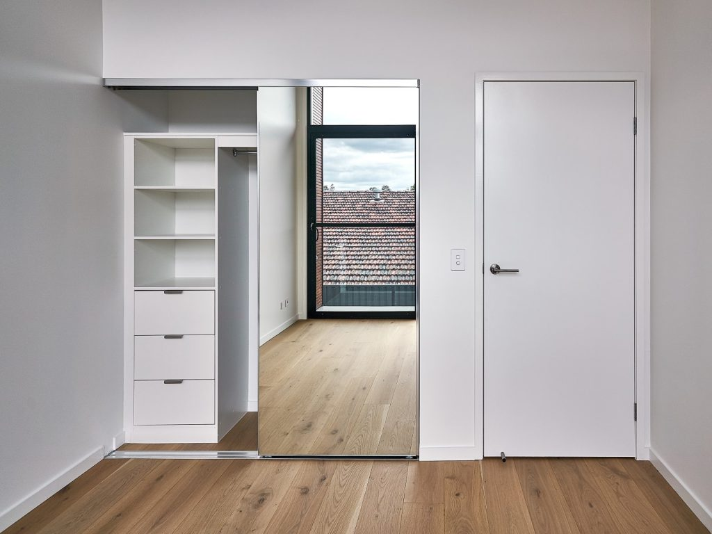 Frameless Mirror Robe Doors with Polished Silver Tracks & Built-in Wardrobe - Standard White Board Shelving with Finger Pull Handles on the Bank of Drawers