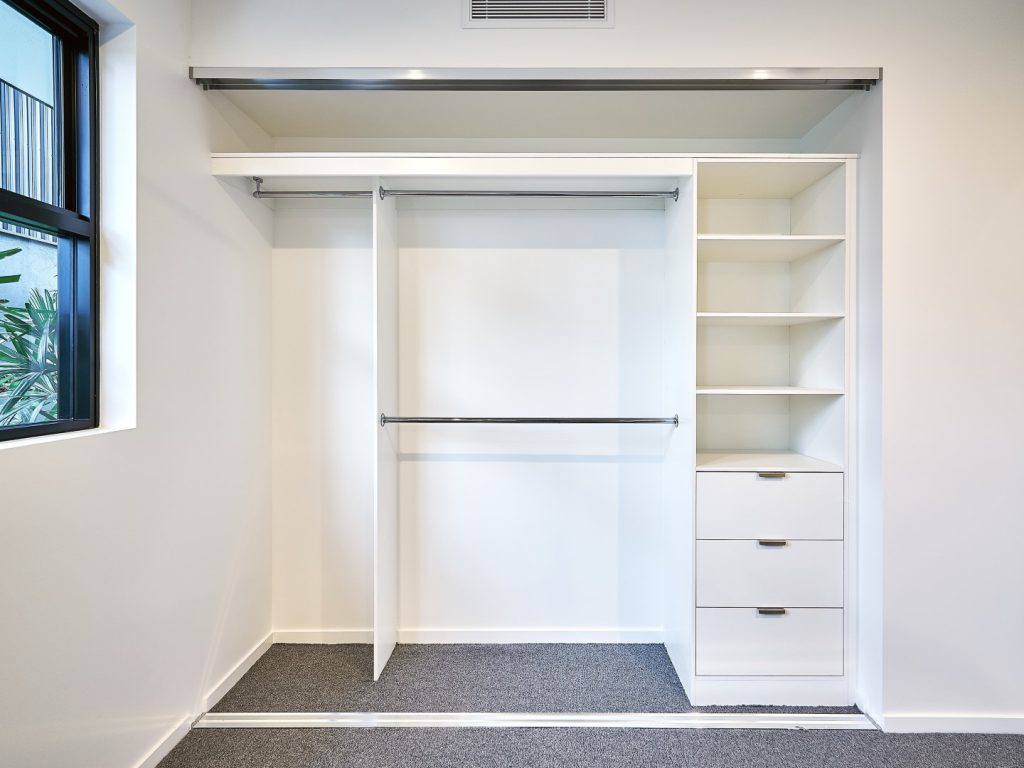 Built-in Wardrobe - Standard White Board Shelving with Finger Pull Handles on the Bank of Drawers & Round Chrome Hanging Rods