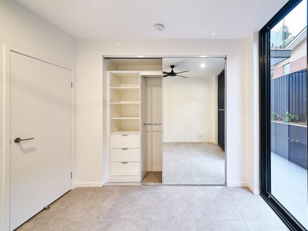 Polished Silver Framed Mirror Robe Doors & Built-in Wardrobe - Standard White Board Shelving with Finger Pull Handles on the Bank of Drawers & Round Chrome Hanging Rods