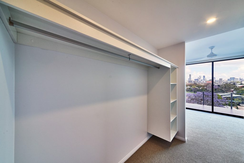 Built-in Wardrobe - Standard White Board Suspended Bank of Shelves, Top Shelf and Round Chrome Hanging Rod