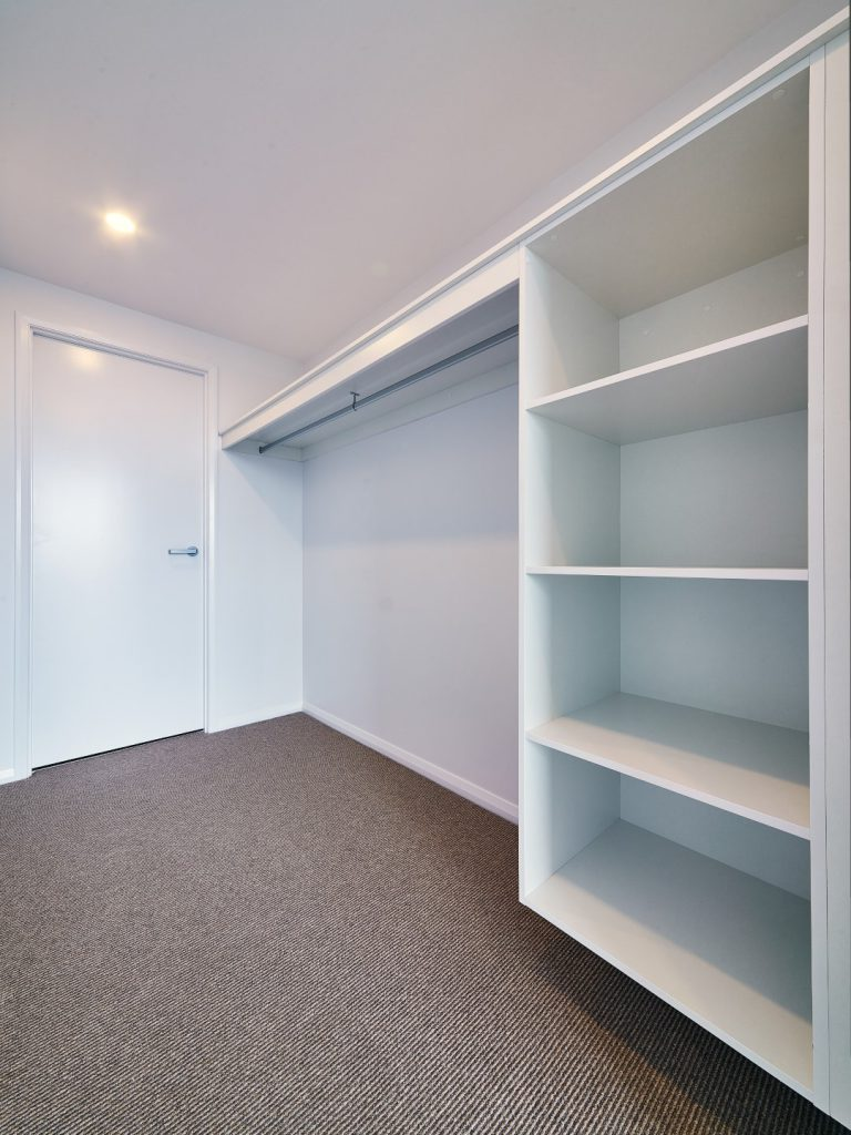 Built-in Wardrobe - Standard White Board Suspended Bank of Shelves, Top Shelf & Round Chrome Hanging Rod