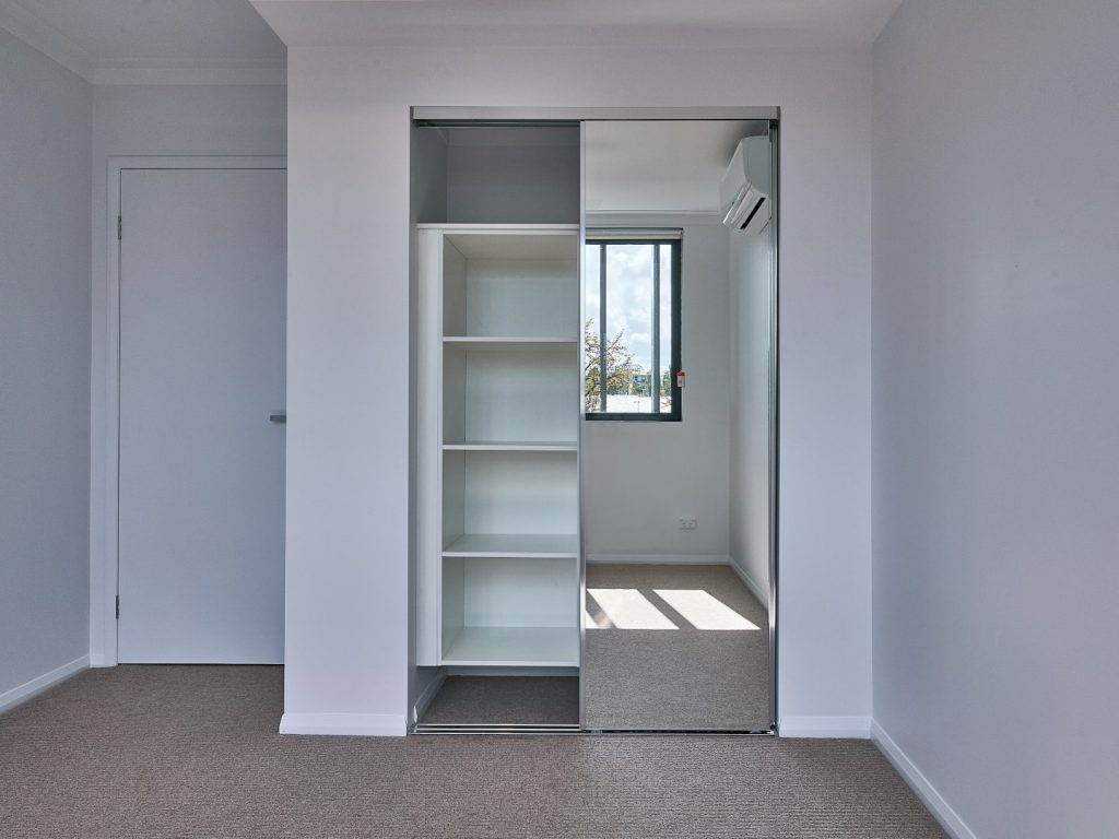 Polished Silver Framed Mirror Robe Doors with a Suspended Bank of Shelves