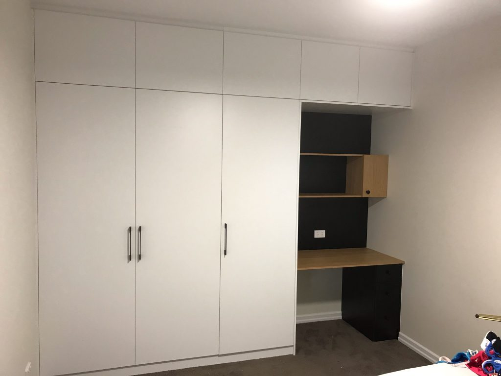 White Board Wardrobe with Hinged Doors and Polished Silver Handles; Extra Storage Cupboards above Wardrobe with a Colour Board Desk on Right Hand Side