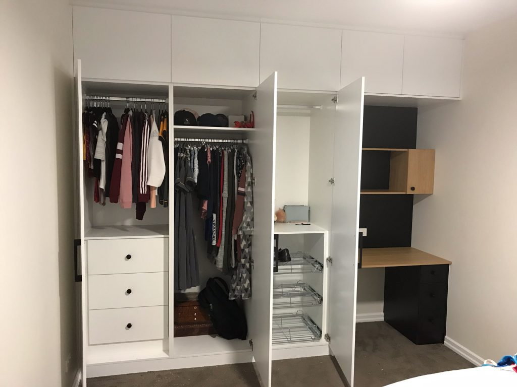 White Board Wardrobe with Hinged Doors, a Bank of Shelves, Chrome Hanging Rods & Sliding Drawers; Extra Storage Cupboards above Wardrobe with a Colour Board Desk on Right Hand Side