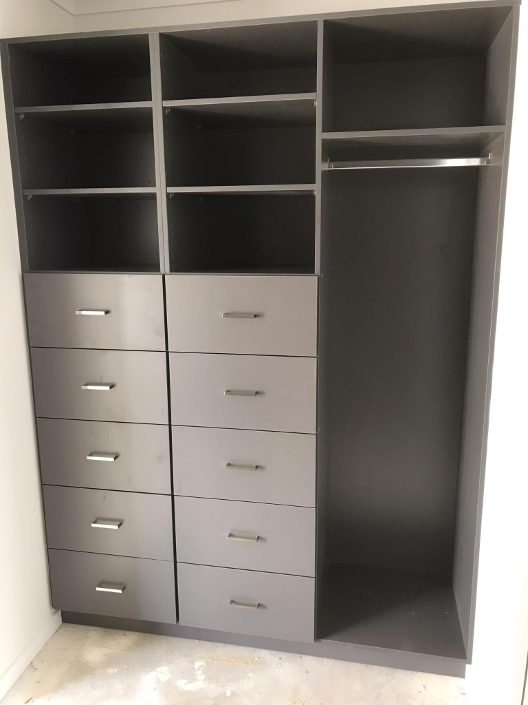Walk-In-Wardrobe - Dark Brown Colour Board Shelving with Finger Pull Handles on the Banks of Drawers