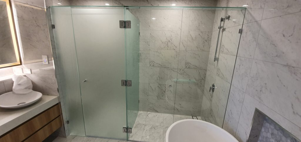Frameless T-Screen for Shower & Toilet Area; LHS Panels are Acid Etched Glass, RHS Panels are Clear Glass, with Polished Silver Hinges