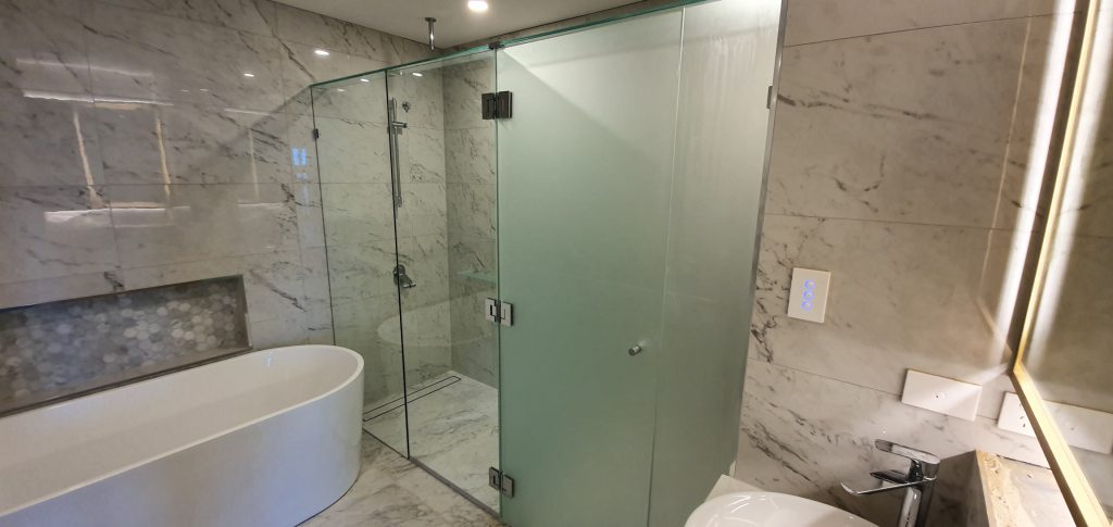 Frameless T-Screen for Shower & Toilet Area; LHS Panels are Clear Glass, RHS Panels are Acid Etched Glass, with Polished Silver Hinges