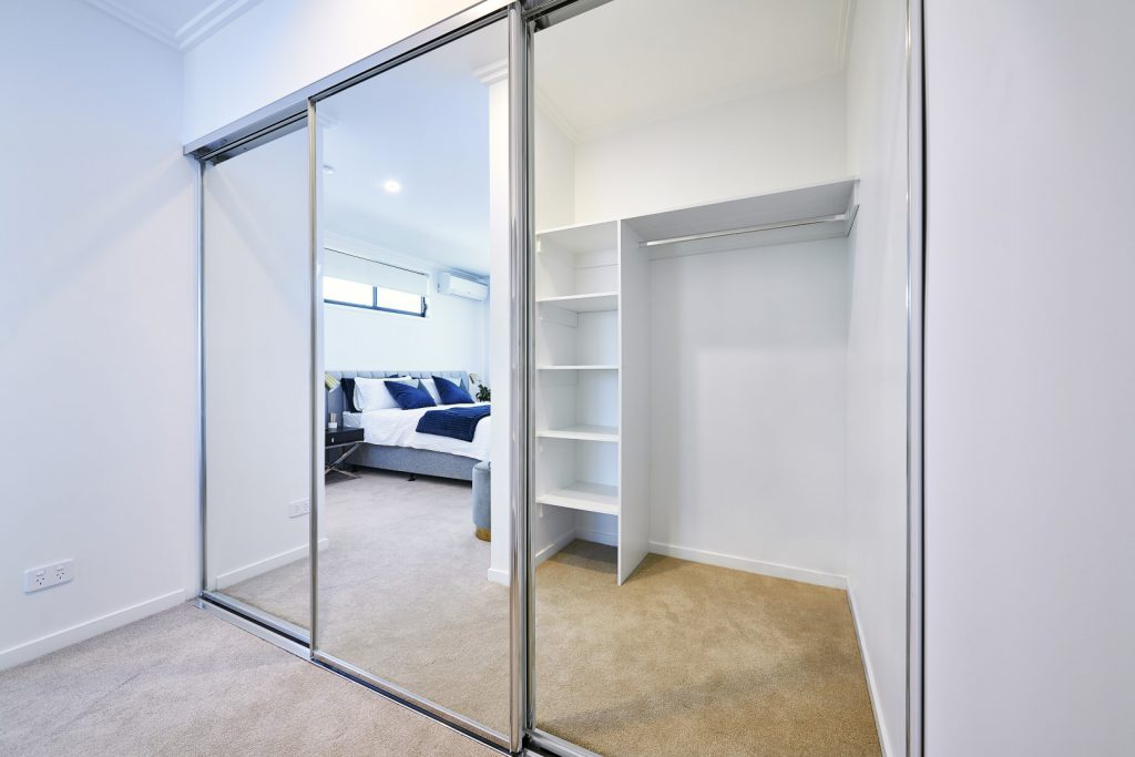 Polished Silver Framed Mirror Robe Doors with Polished Silver Tracks, White Board Shelving, Top Shelf & Chrome Hanging Rod Opposite (in reflection of Mirror Robe Doors)