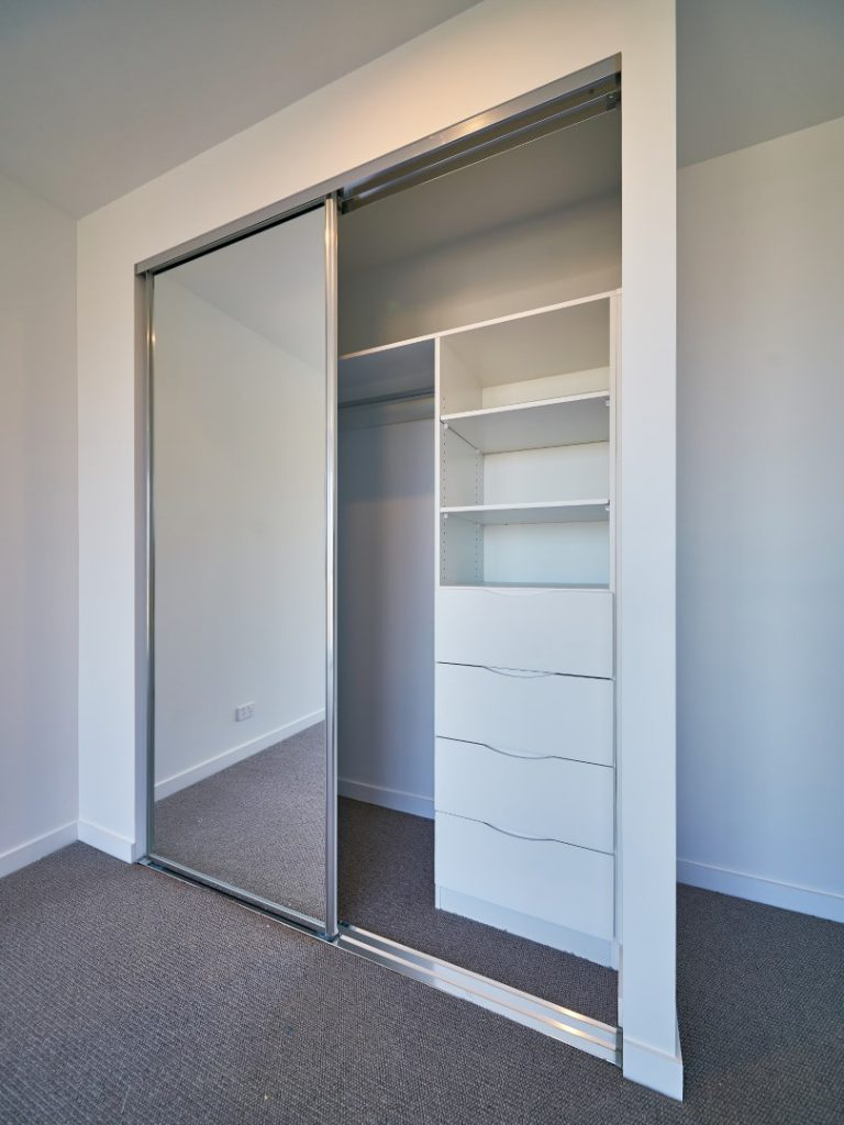 Mirror Robe Doors with Polished Silver Frame & Polished Silver Tracks with Standard White Board Shelving and a Bank of Drawers