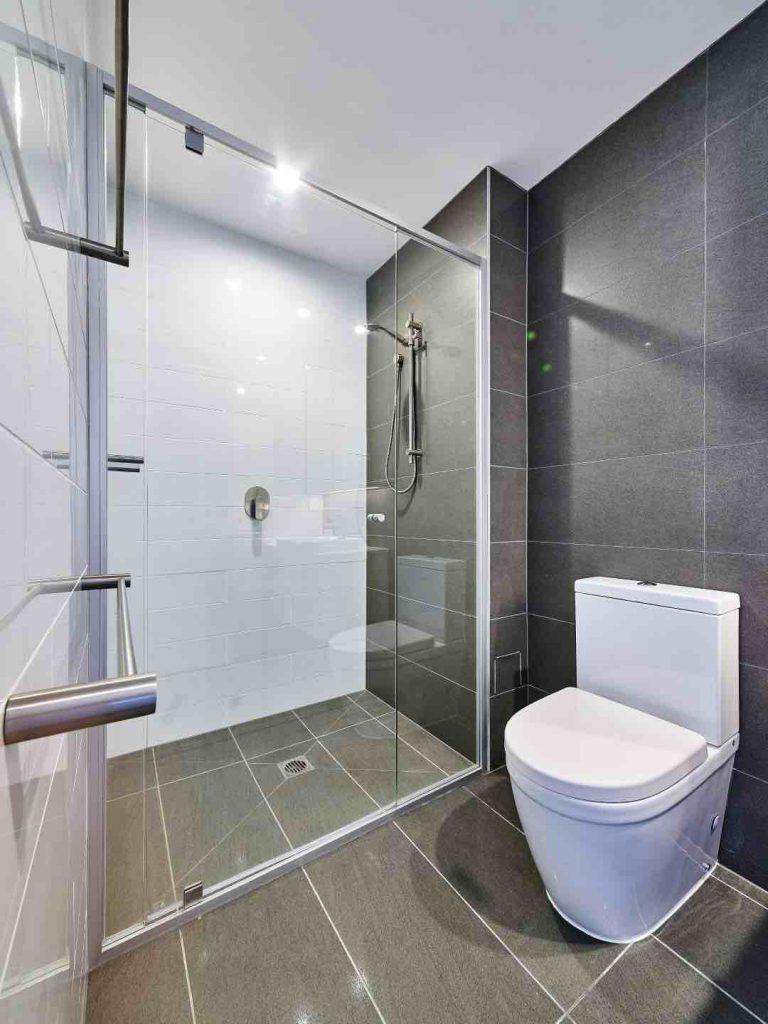 Vogue Semi Frameless Shower Screen Installed In Grey Tiled Bathroom