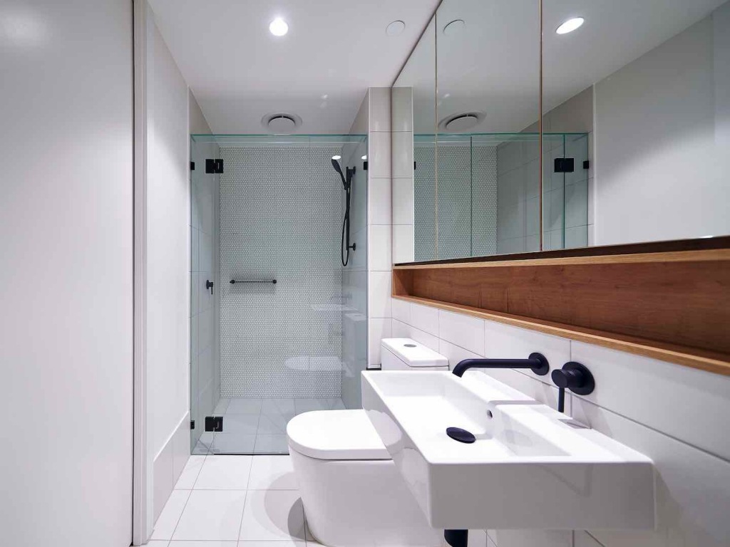 Frameless Shower Screen With Black Fittings installed in white bathroom with mirror shaving cabinet